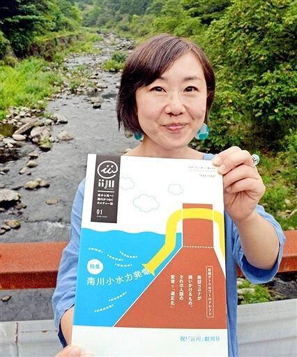 「ii川」創刊号を持つ編集長。背景は南川上流地点=福井県おおい町名田庄納田終