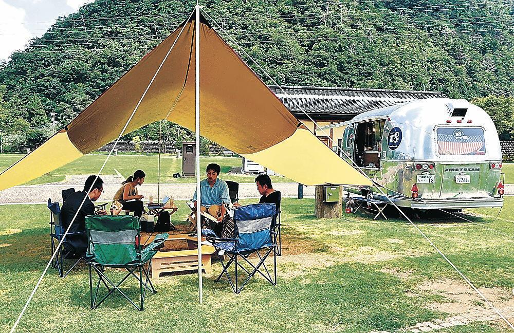 テントの中で仕事を進める参加者=白山市吉野の吉野オートキャンプ場