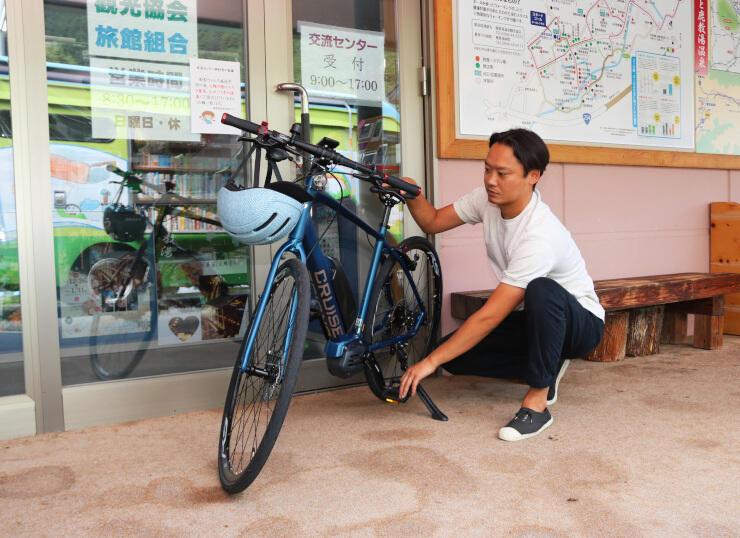 電動アシスト自転車の状態を確認する中瀬さん。日帰りプランの利用者に無料で貸し出す=25日、上田市