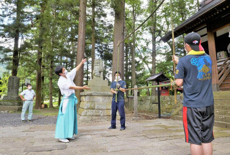 竹の棒を組み、仕掛け花火の設置場所を決める押森宮司(左から2番目)ら