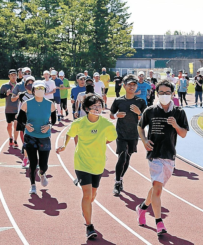 野口さん(中央)と一緒にトラックを走る参加者=金沢市の県陸上競技場サブグラウンド