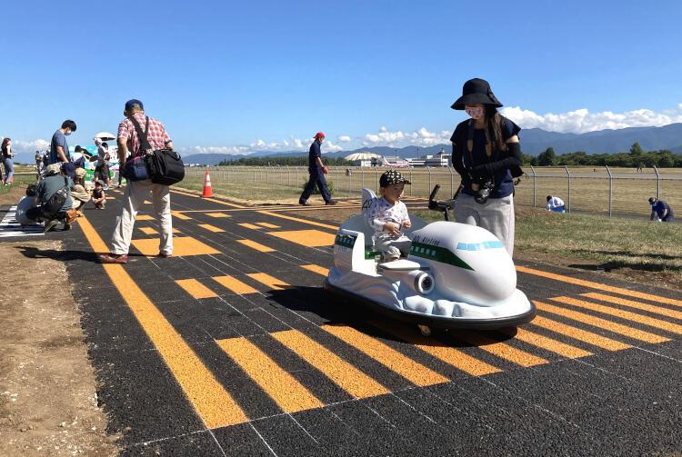 「開港式」が行われたミニ滑走路で早速遊ぶ来場者=5日、県松本平広域公園