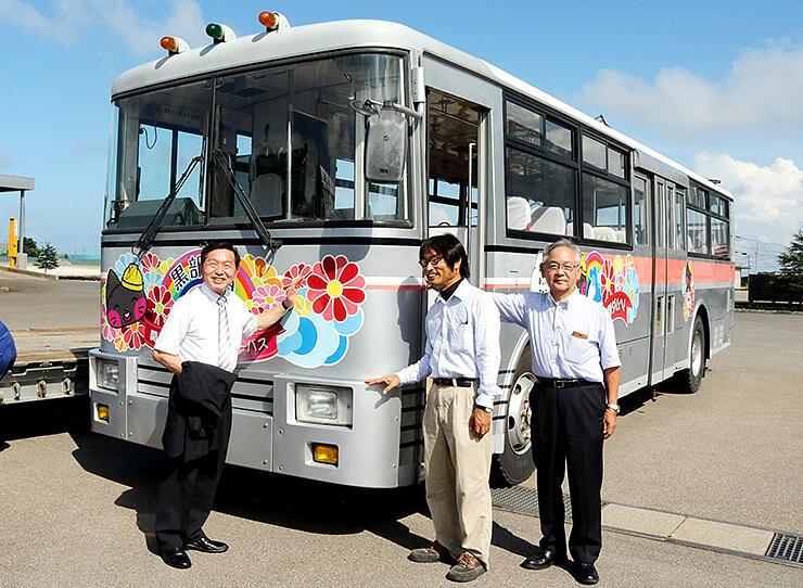 大町へ里帰りするトロバスを囲む(左から)牛越大町市長、善光さん、高倉社長=日本総合リサイクル