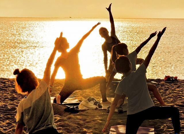 沈む夕日を眺めながらヨガを楽しむ参加者=9月6日、福井県坂井市の三国サンセットビーチ