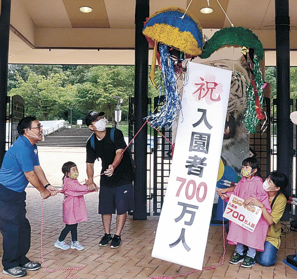 松島園長(左)とくす玉を割る作田恵菜ちゃん(右から2人目)、未奈ちゃん(左から2人目)ら家族=能美市のいしかわ動物園