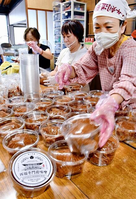 手際よくみそをパッケージ詰めする奉賛会の会員ら=9月14日、福井県敦賀市原の西福寺