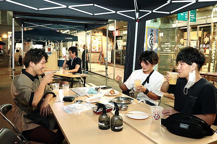 歩行者天国になった市道に設けたテントで飲食を楽しむ若者たち
