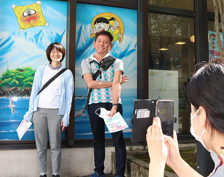 スマートフォンにキャラクターを取り込み記念撮影する「謎解きラリー」の参加者