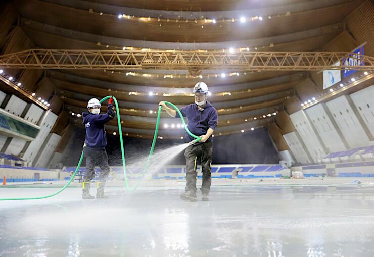 リンクの製氷作業が始まったエムウェーブ。温水をまいて少しずつ厚みを増していく=21日午後6時41分、長野市
