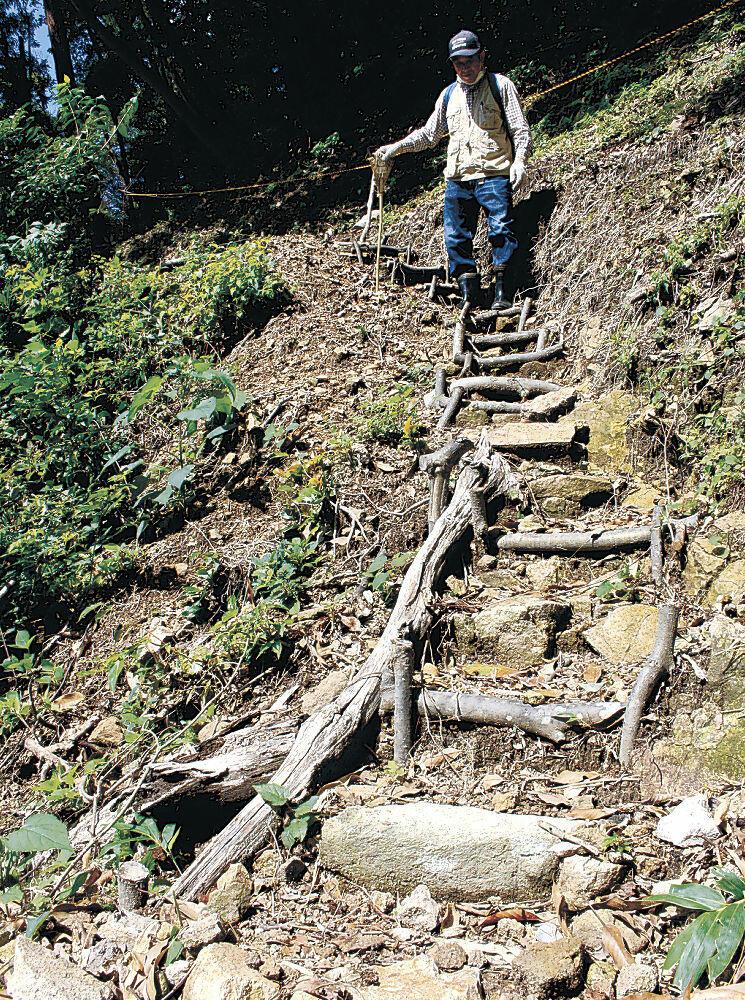 洞窟へ続く遊歩道に設けた階段を確認する角さん=小松市那谷町