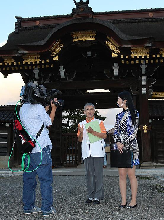 カメラの前で見どころを解説する金子会長(中央)=勝興寺