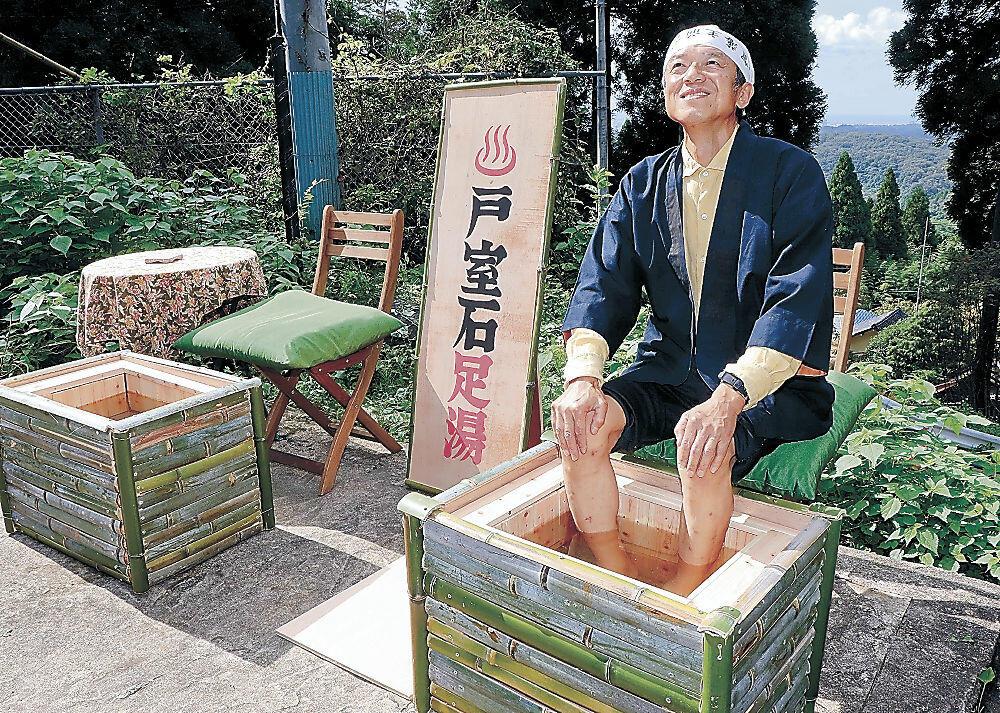 自身が考案した戸室石を用いた足湯に漬かる丸山さん=清水町