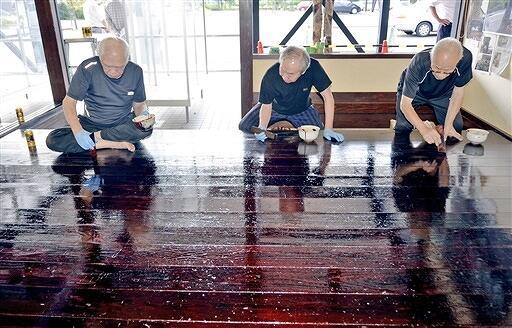 床を漆で塗装する伝統工芸士=9月23日、福井県鯖江市うるしの里会館の職人工房