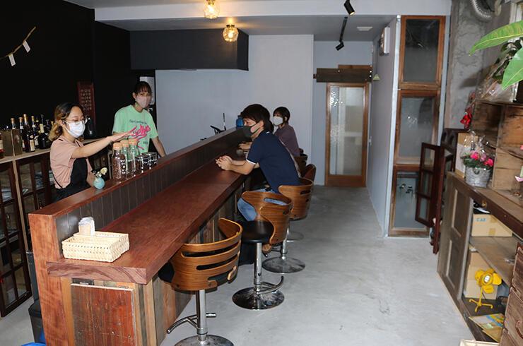 オープンしたカフェで、客にコーヒーの説明をする(左から)阿部さんと平岡さん
