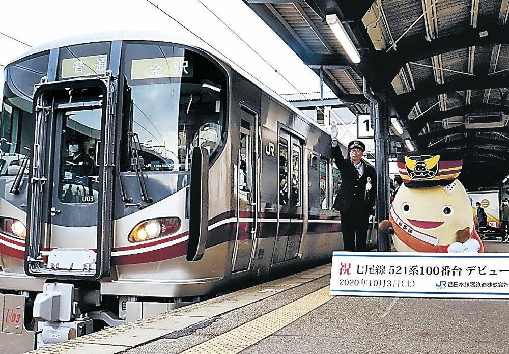 列車を見送る佐原駅長(左)とわくたまくん=JR七尾駅