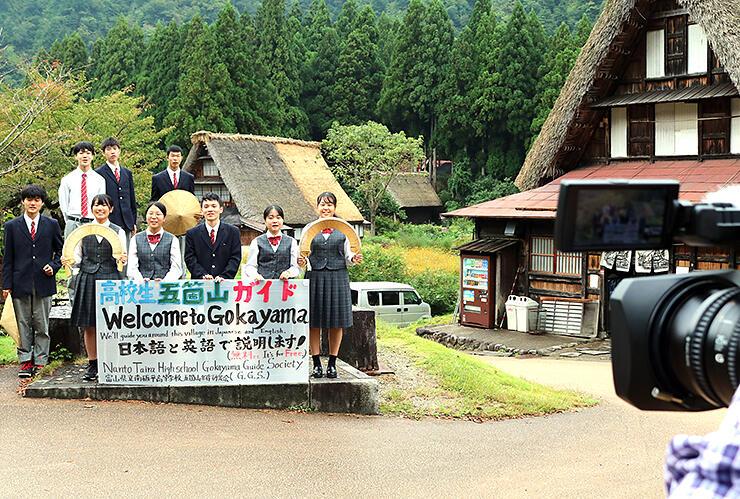 9人全員で集落の魅力を紹介する部員たち=南砺市菅沼