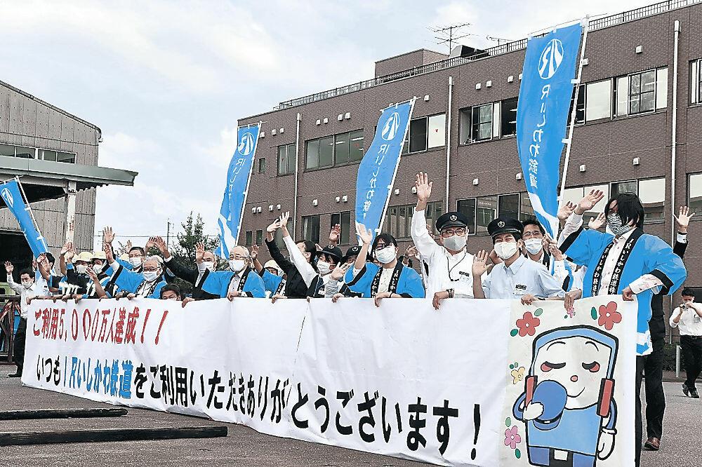 5千万人の達成車両に向かって手を振る社員=金沢市高柳町のIRいしかわ鉄道本社