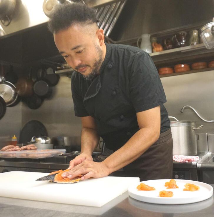 下味を付けた信州サーモンを切り分け、カルパッチョを作る檀野さん=京都市中京区