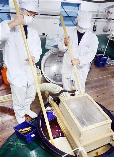 櫂棒を使って手際よく新酒を仕込む蔵人=10月9日、福井県勝山市の一本義久保本店