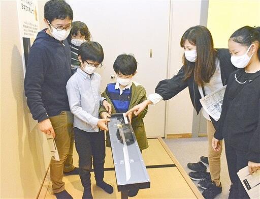 ケースに入った刀を傾け、刃文を鑑賞する来場者=10月10日、福井県福井市立郷土歴史博物館