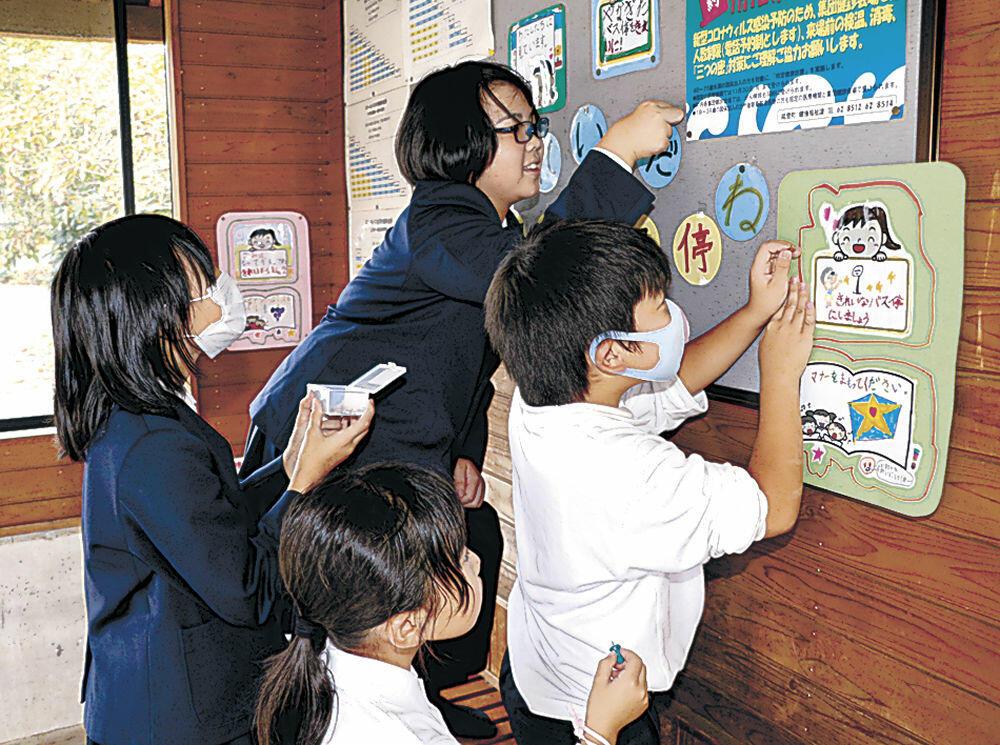 ポスターを掲示する児童=能登町柳田