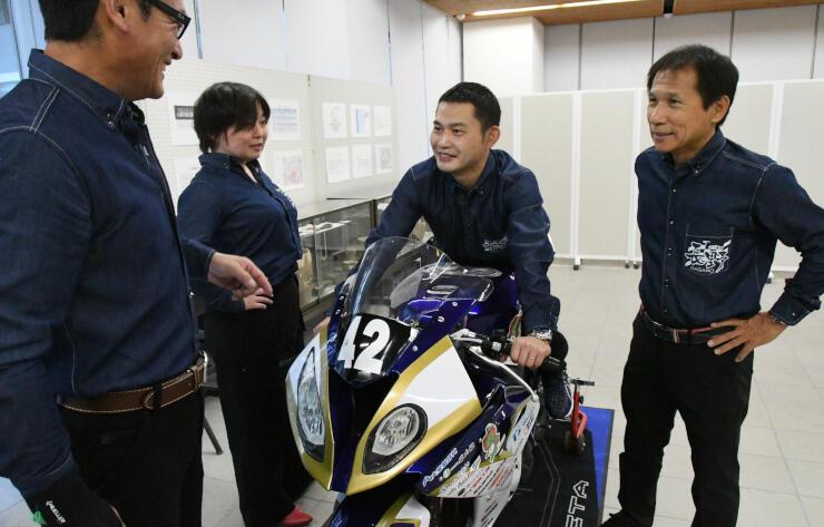 マシンに乗る桜山さんと、チーム長野のメンバー