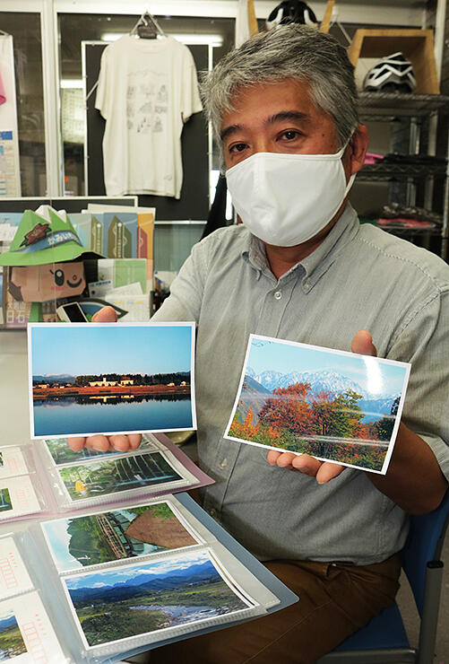 上市町観光案内所で販売しているポストカードを持つ澤井事務局長