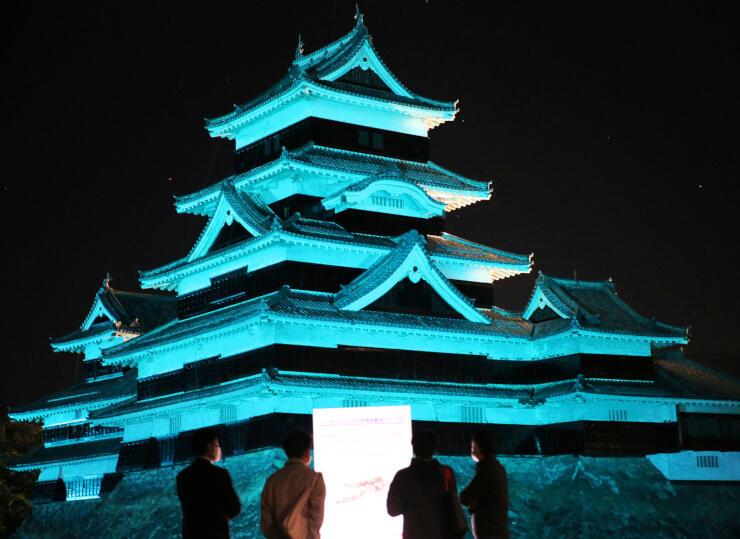 「世界骨粗しょう症デー」に合わせて青色にライトアップされた松本城=20日夜