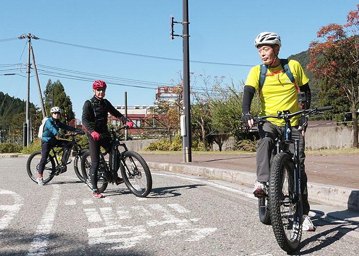 E-バイクで立山駅を出発する舟橋町長(右)ら
