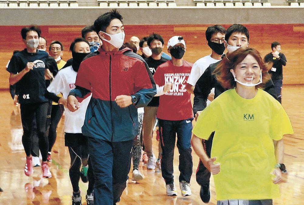 講師と一緒に走って練習方法を学ぶペースランナーセミナーの参加者=市総合体育館