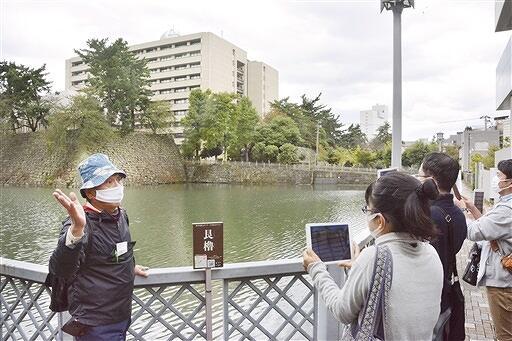 福井城址を歩き、CG映像を見ながら吉田客員教授(左)の話を聞くツアー参加者=10月25日、福井県福井市大手2丁目
