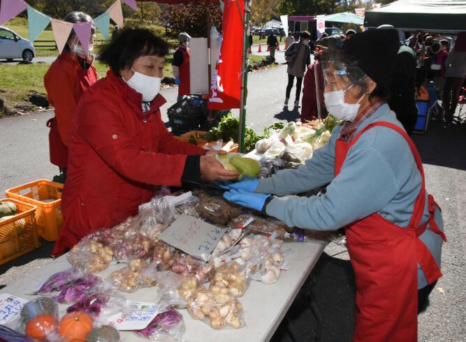 セロリやカボチャ、キクイモなどさまざまな野菜が並んだ農家有志のブース