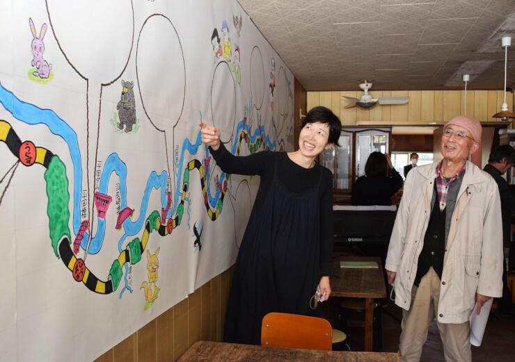 店内に橋爪さん(右)が描いた飯田線の路線図を貼り笑顔を見せる尾崎さん