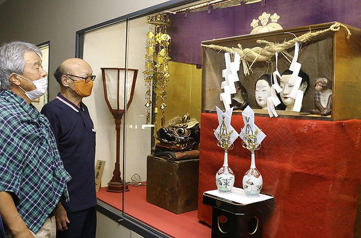 特別展示中の御神像を見つめる東町曳山保存会のメンバー