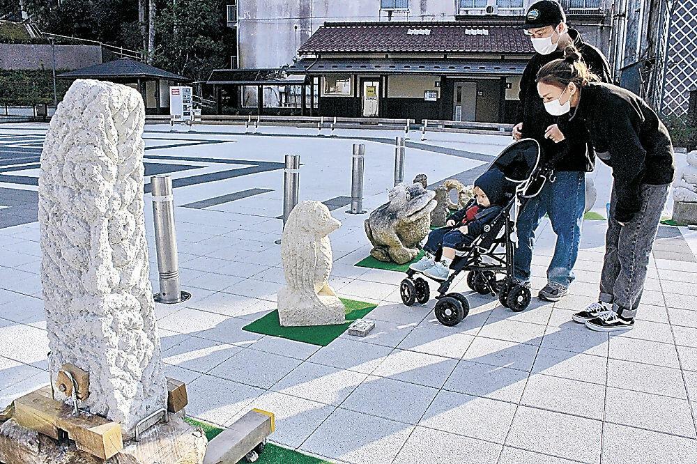 石の彫刻作品を楽しむ親子=小松市粟津町