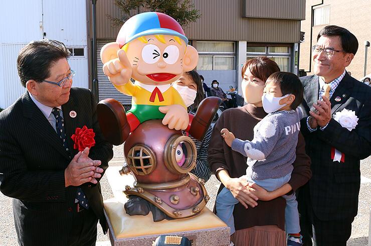 除幕された怪物くんのモニュメントに笑顔を見せる親子と林市長(右)、倉品顧問(左)=氷見市のJR氷見駅前