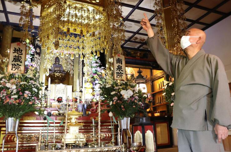 12年ぶりに姿を現した西生寺の阿弥陀如来と、本尊の手に結ばれた綱を指さす阿刀隆峰住職=長岡市寺泊野積