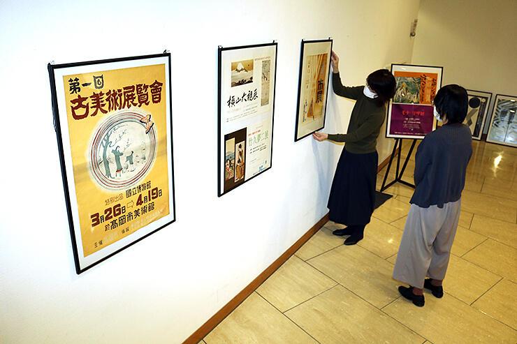 昭和時代の美術展ポスターの展示準備をする関係者