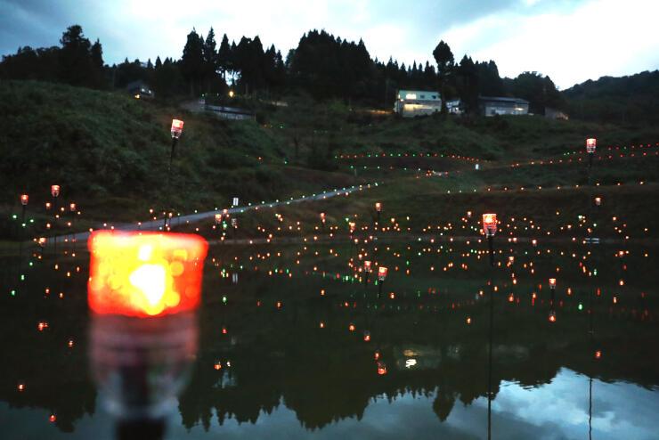 電球が水面を彩る「棚田棚池あかりのページェント」=長岡市山古志虫亀