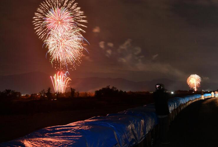 土のうが並ぶ千曲川の堤防決壊現場近くから望む「復興花火」。地元住民も見上げた=3日午後6時35分、長野市津野