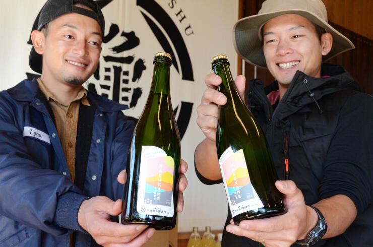 銀賞、銅賞を受賞した自家醸造のシードルを手にする井口さん(左)と兄の北沢さん