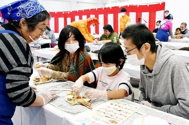 「ふくい農林水産まるごとフェスタ」で、セイコガニの食べ方を学ぶ親子ら=11月14日、福井市の福井県産業会館