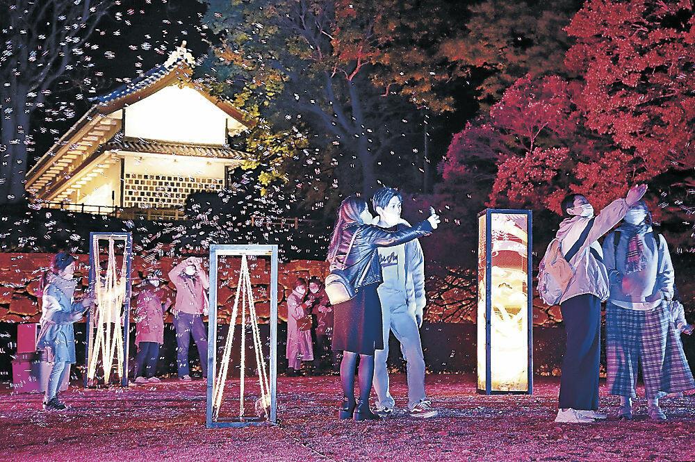 シャボン玉とライトアップの幻想的な演出を楽しむ来園者=金沢城公園