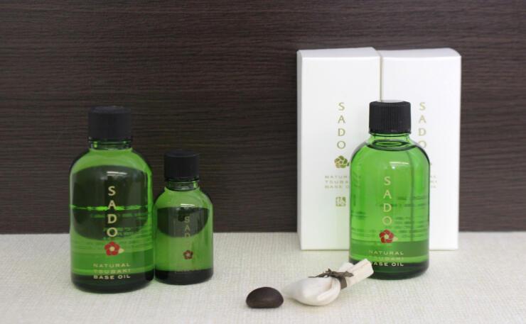 佐渡のヤブツバキの種(中央)を搾ったオイル「SADO」。65グラム瓶には小袋に入った種が付いている