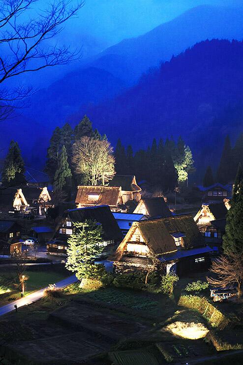 山あいにライトアップで照らされる合掌造り集落=南砺市相倉