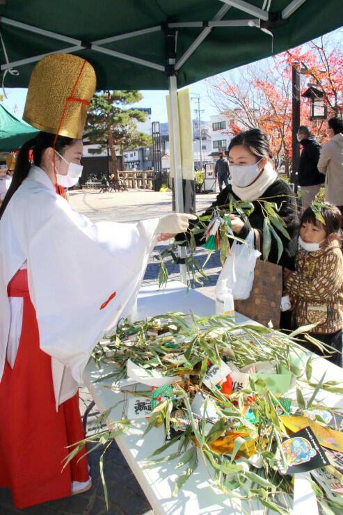 さまざまな縁起物を飾り付けた「縁起笹」を買い求める人たち