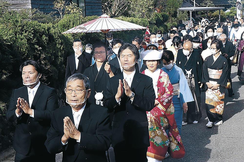 傘を差す久保さん(中央)夫妻の前途を祝し、七尾まだらを披露する会員(手前)=七尾市古府町