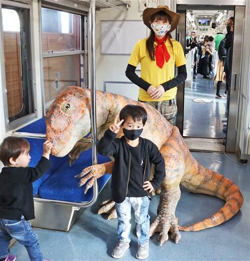 新たに加わったフクイラプトルの恐竜モニュメントやアテンダントと出発前に記念撮影する子どもたち=11月22日、福井市のえちぜん鉄道福井駅
