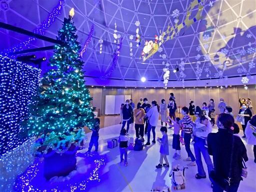 家族連れが見守る中、ライトアップされたクリスマスツリー=11月22日、福井県坂井市の県児童科学館