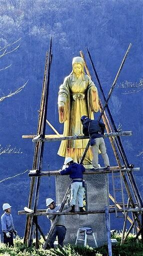 青空の下、雪囲いに覆われる麻那姫像=11月24日、福井県大野市下若生子